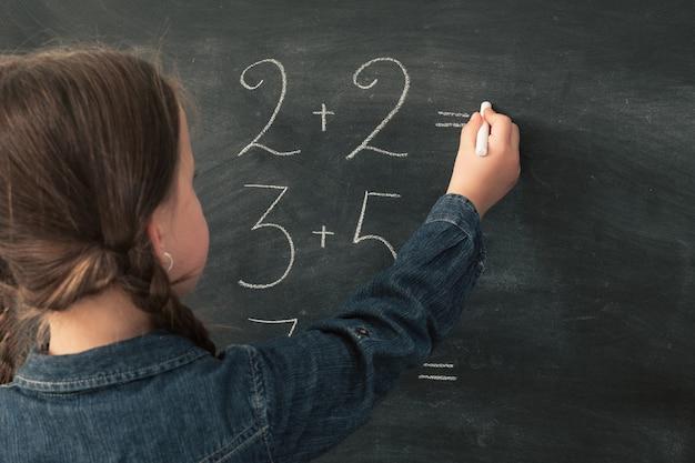 Scolara che scrive le somme di matematica in gesso sulla lavagna
