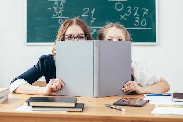 Studentesse che si nascondono dietro il libro che si siede in un'aula.