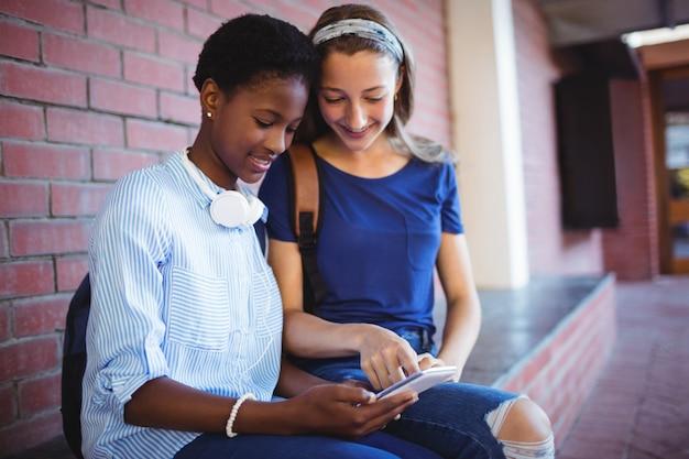 Studentesse seduti contro un muro di mattoni e utilizzando il telefono cellulare