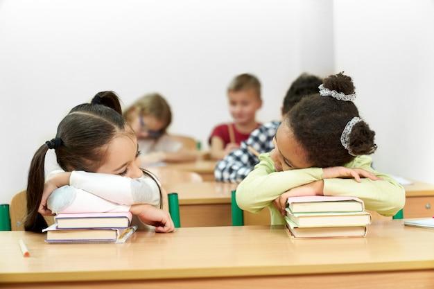 Studentesse che dormono in aula alla scrivania, appoggiandosi sui libri.