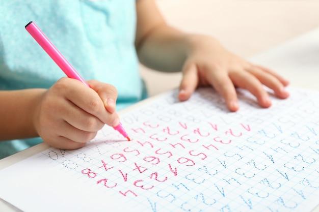 Schoolkid impara a scrivere su un foglio di carta, primo piano