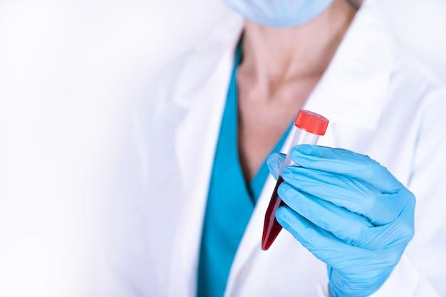 Concetto di scienza, chimica, biologia, medicina e persone - primi piani di giovane scienziato femminile che tiene la provetta con campione di sangue che fa ricerca nel laboratorio clinico