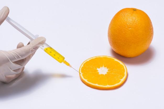 Esperimento scientifico con arancia e siringa isolata su bianco.