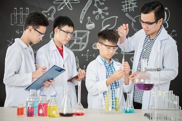 Insegnante di scienze che aiuta lo studente ad aggiungere il reagente in provetta con contagocce, altri ragazzi che guardano e prendono appunti