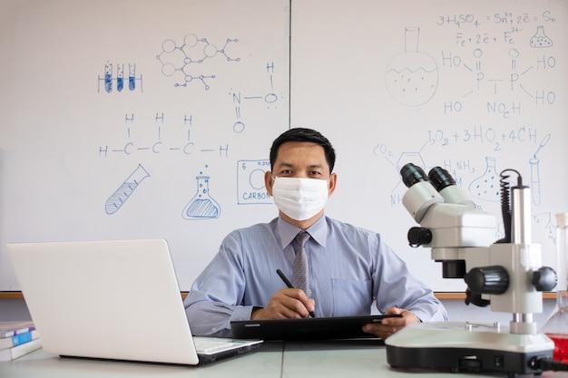 Insegnante di scienze che insegna in classe con maschera facciale