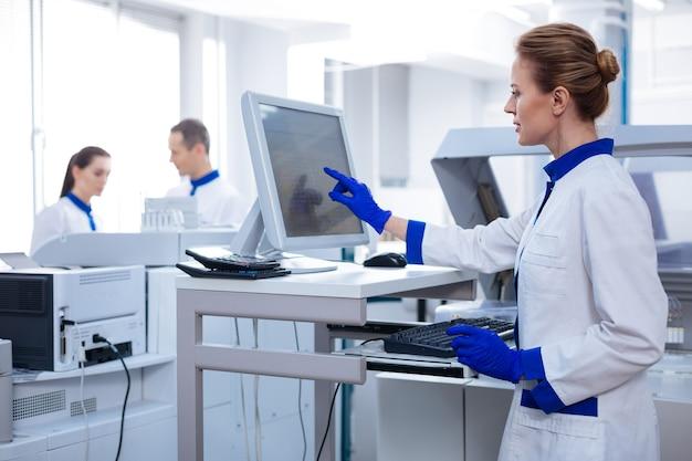 Scienza per le donne. ricercatore femminile bello biondo che riempie la cartella medica mentre esamina lo schermo e che si leva in piedi nel laboratorio