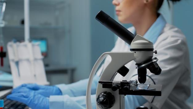 Donna scientifica con lo strumento del microscopio che studia la capsula di petri