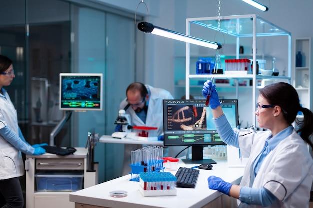 Scienziato che analizza il campione di sangue in provetta e gruppo che fa ricerca con l'immagine del dna