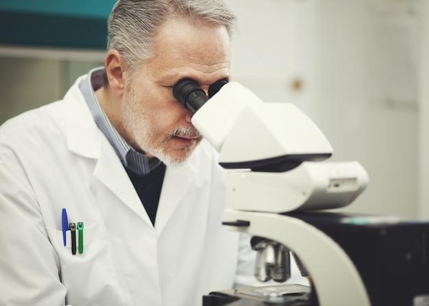 Scienziato conducendo ricerche guardando attraverso il microscopio