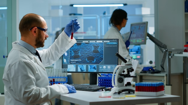 Scienziato che esamina campioni di sangue e liquidi che lavorano in un moderno laboratorio attrezzato. team di medici che analizzano l'evoluzione del vaccino utilizzando la diagnosi di ricerca ad alta tecnologia contro il covid19