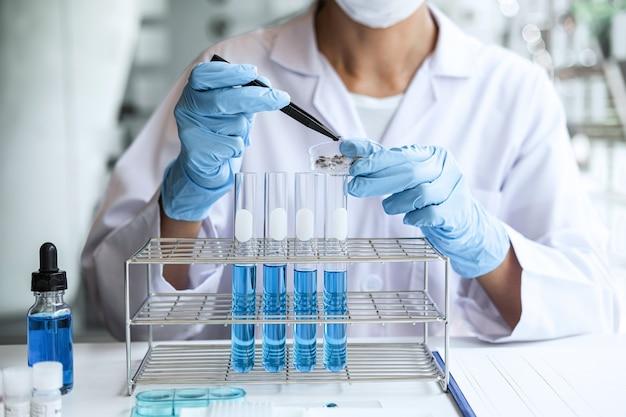 Scienziato o medico in camice da laboratorio che tiene il contagocce con il reagente, mescolando i reagenti nel pallone di vetro