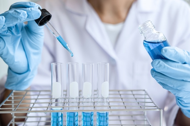 Scienziato o medico in camice da laboratorio con provetta con reagente