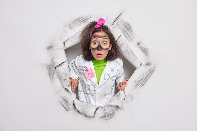 Scienziato farmacologo sviluppa un nuovo tipo di medicina o cosmetico stordito per ottenere risultati inaspettati dell'esperimento indossa pose uniformi attraverso il buco della carta svolge ricerche scientifiche