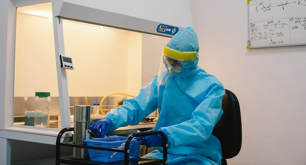 Uno scienziato in esperimento di campione di pipettaggio uniforme di sicurezza ppe nella cabina di sicurezza biologica