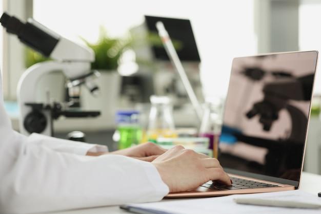 Scienziato o studente che utilizza computer portatile e microscopio apprendimento online apprendimento online