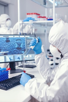 Scienziato che preleva il campione di sangue dalla provetta usando la micropipetta. medico che lavora con vari batteri e tessuti, ricerca farmaceutica per antibiotici contro covid19.