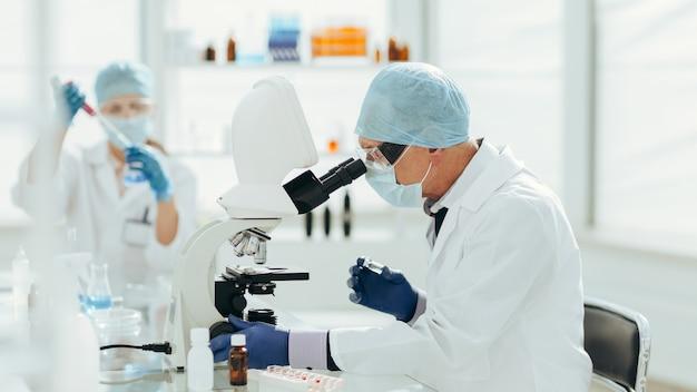 Scienziato che utilizza un microscopio in un laboratorio biochimico