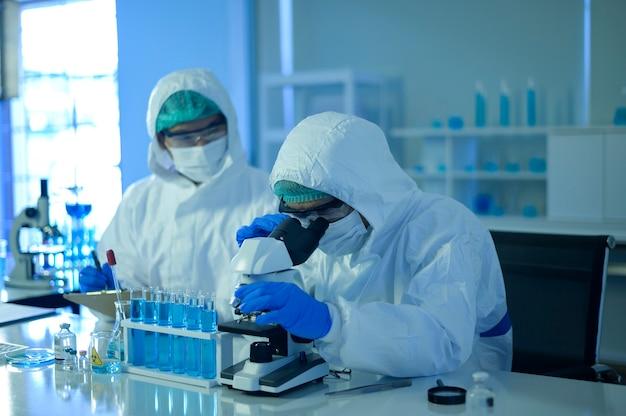 Uno scienziato che utilizza il microscopio durante l'esperimento in laboratorio