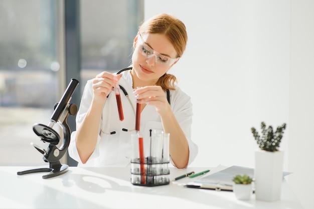 Scienziato che utilizza un microscopio in un laboratorio, test per il vaccino contro il coronavirus covid19