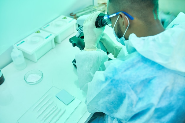 Scienziato using microscope nel laboratorio medico
