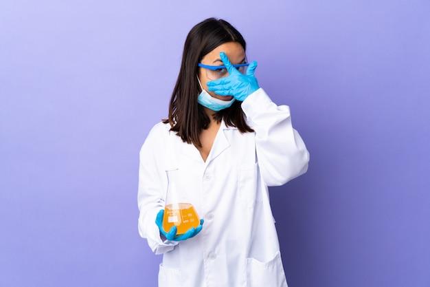Donna scienziato che studia un vaccino per curare la malattia coprendo gli occhi con le mani e sorridendo