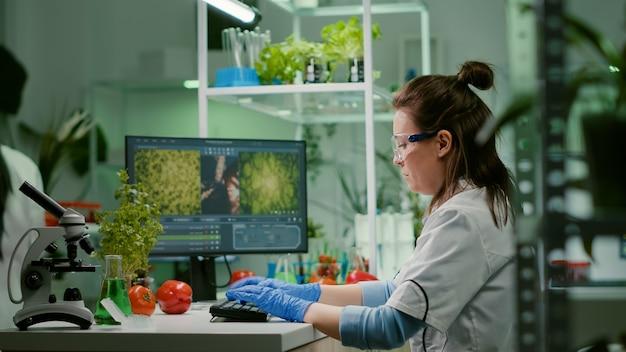 Ricercatore donna scienziato digitando competenze biochimiche sul computer per esperimento di microbiologia. equipe medica che lavora in un laboratorio farmaceutico analizzando la mutazione genetica
