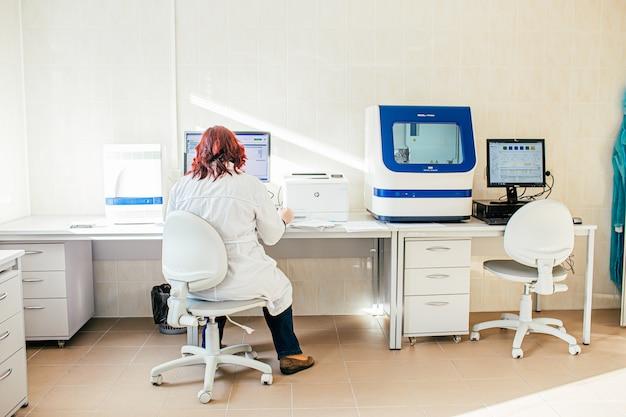Donna scienziato in camice bianco che lavora in laboratorio biologico o medico con analizzatore di dna, preparando al test del dna.