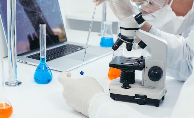 Lo scienziato lavora con un microscopio in un laboratorio medico