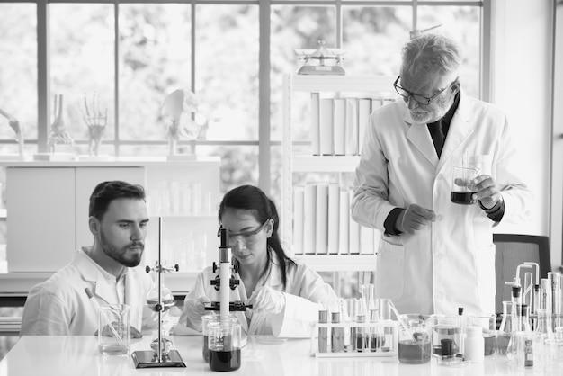 Gli scienziati stanno lavorando nei laboratori di scienza. primo piano di uno scienziato. giovane scienziato femminile che guarda attraverso un microscopio in un laboratorio che fa ricerca, analisi microbiologica,