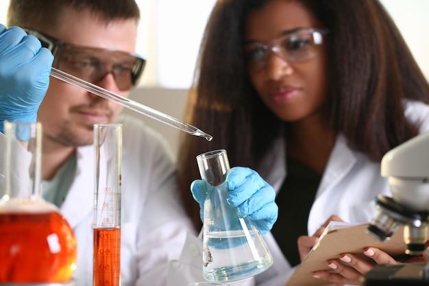 Gli scienziati in laboratorio tengono la beuta e vi gocciolano del liquido trasparente.