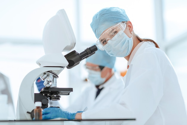 Scienziati che testano il liquido e scrivono i risultati in un giornale di laboratorio