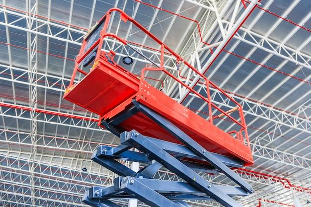 Piattaforma elevatrice a forbice con sistema idraulico elevato verso un tetto di fabbrica