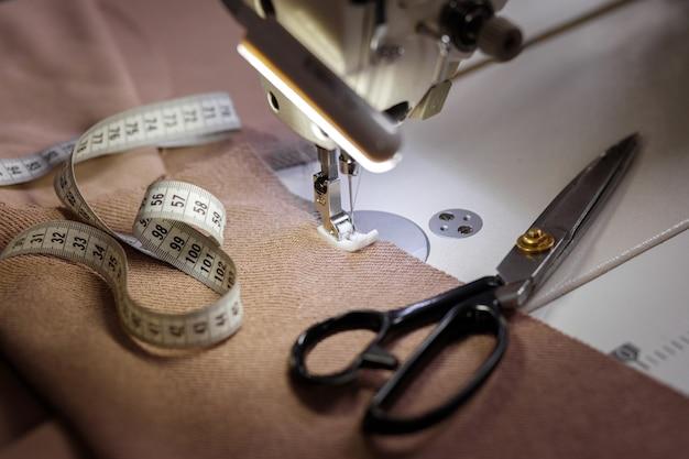 Forbici, centimetro e macchina da cucire sul tavolo