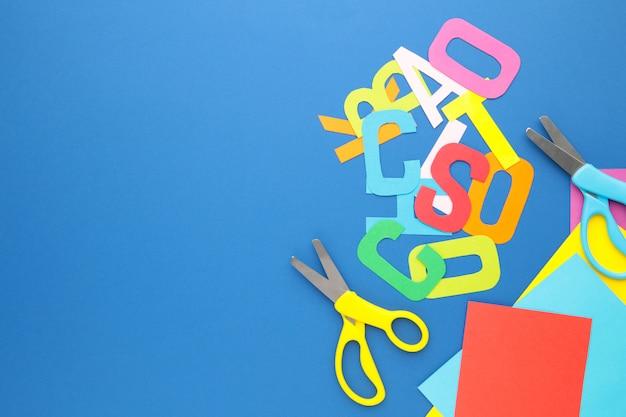 Forbici e carta colorata per l'arte dei bambini sulla parete blu