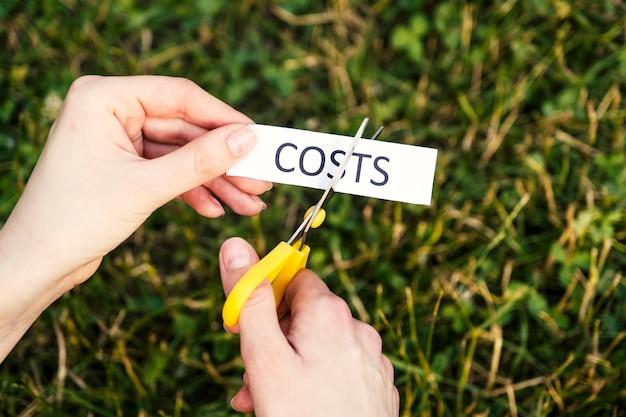 Le forbici tagliano un pezzo di carta che dice costi