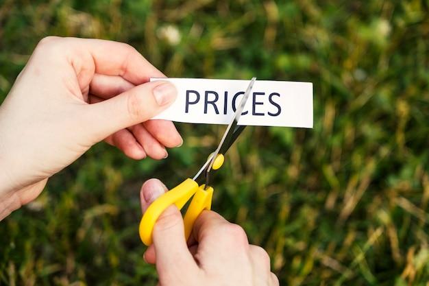 Le forbici tagliano un pezzo di carta che dice i prezzi