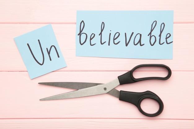 Forbici che tagliano carta bianca con il testo non credibile, cambia la parola in credibile