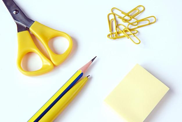 Forbici, matita, penna, graffette, carta per appunti su una superficie bianca