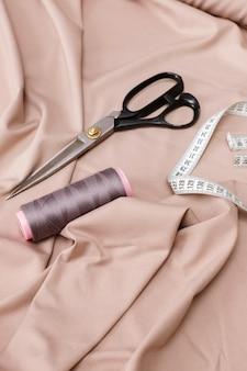 Filo delle forbici e centimetro su uno sfondo di tessuto