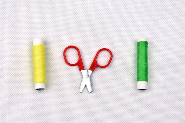 Forbici e fili su sfondo bianco