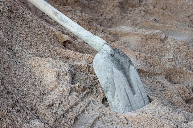 Pala a cucchiaio spalmato di cemento in un mucchio di sabbia per fare cemento.