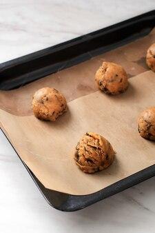 Miscela di biscotti con scaglie di cioccolato crudo scavata sulla teglia con carta da forno, pronta da cuocere
