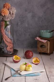 Palline di passione, vaniglia e gelato alla fragola su un piatto bianco su un tavolo di legno