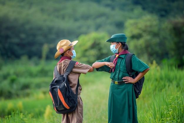 Scout studenti asiatici che indossano uniformi e maschera