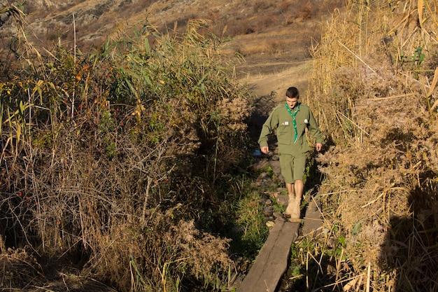 Scout o ranger che attraversa un ponte di tronchi caduto attraverso un fiume o un burrone camminando con cautela lungo il tronco bilanciandosi dalla caduta