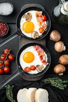 Uova strapazzate in padella con lardo di maiale, pane e piume verdi in padella in ghisa, sul fondo della tavola in legno nero, vista dall'alto laici piatta