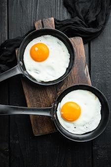 Uova strapazzate in padella con strutto di maiale, pane e piume verdi in padella in ghisa, sul tavolo in legno nero tabella, vista dall'alto laici piatta