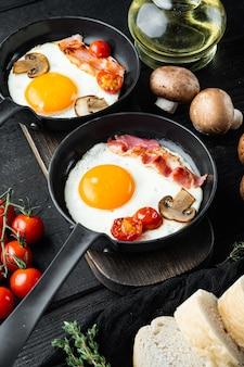 Uova strapazzate in padella con strutto di maiale, pane e piume verdi in padella in ghisa, su tavola di legno nero