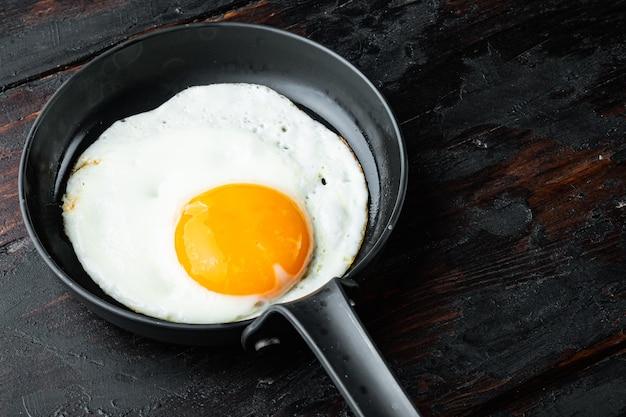 Uova strapazzate in padella con lardo di maiale, pane e piume verdi in padella in ghisa, sul vecchio fondo di tavola in legno scuro,