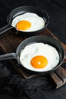 Uova strapazzate in padella con pane di lardo di maiale e piume verdi in padella in ghisa